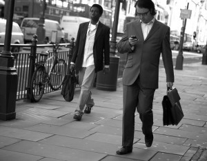 Business Man Checking His Phone as He Walks down the Street