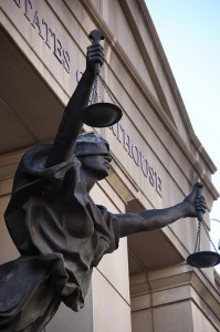 Justice Holding the Scales in Front of a Courthouse